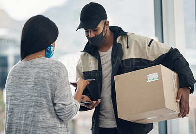 Buy stock photo Shot of a masked young man and woman using smartphones during a home delivery