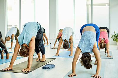 Buy stock photo Shot of a group of men and women practicing the downward facing dog pose during a yoga class