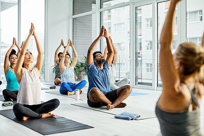 Buy stock photo Shot of a group of men and women practicing yoga in a fitness class