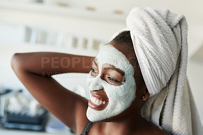 Buy stock photo Shot of a young woman wearing a face mask and a towel wrapped around her hair at home