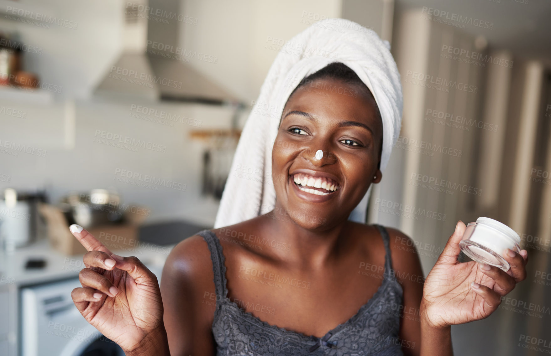 Buy stock photo Shot of a beautiful young woman holding up a face cream product
