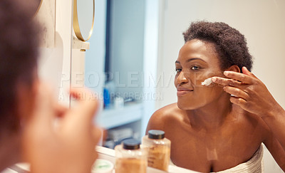 Buy stock photo Shot of a beautiful young woman applying moisturiser while looking in the bathroom mirror