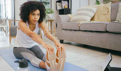 Buy stock photo Shot of a young woman using a digital tablet while exercising at home