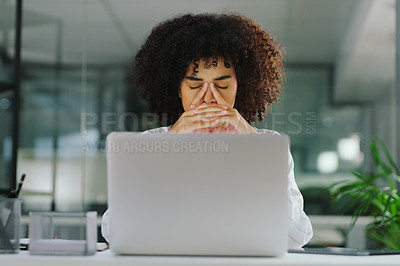 Buy stock photo Shot of a young businesswoman looking stressed while using a laptop in a modern office