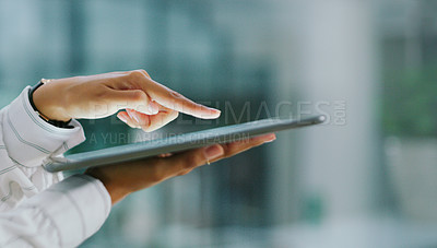 Buy stock photo Shot of an unrecognisable businesswoman using a digital tablet in a modern office
