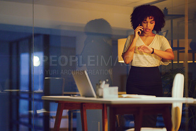 Buy stock photo Shot of a young businesswoman using a smartphone and looking at the time during a late night at work