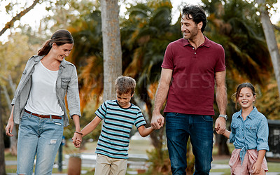 Buy stock photo Shot of a couple with two kids taking a walk through the park together