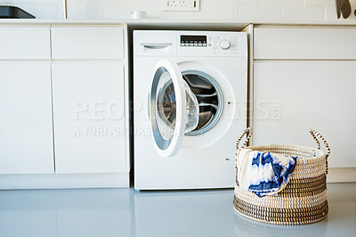 Buy stock photo Shot of a laundry basket standing in front of a washing machine