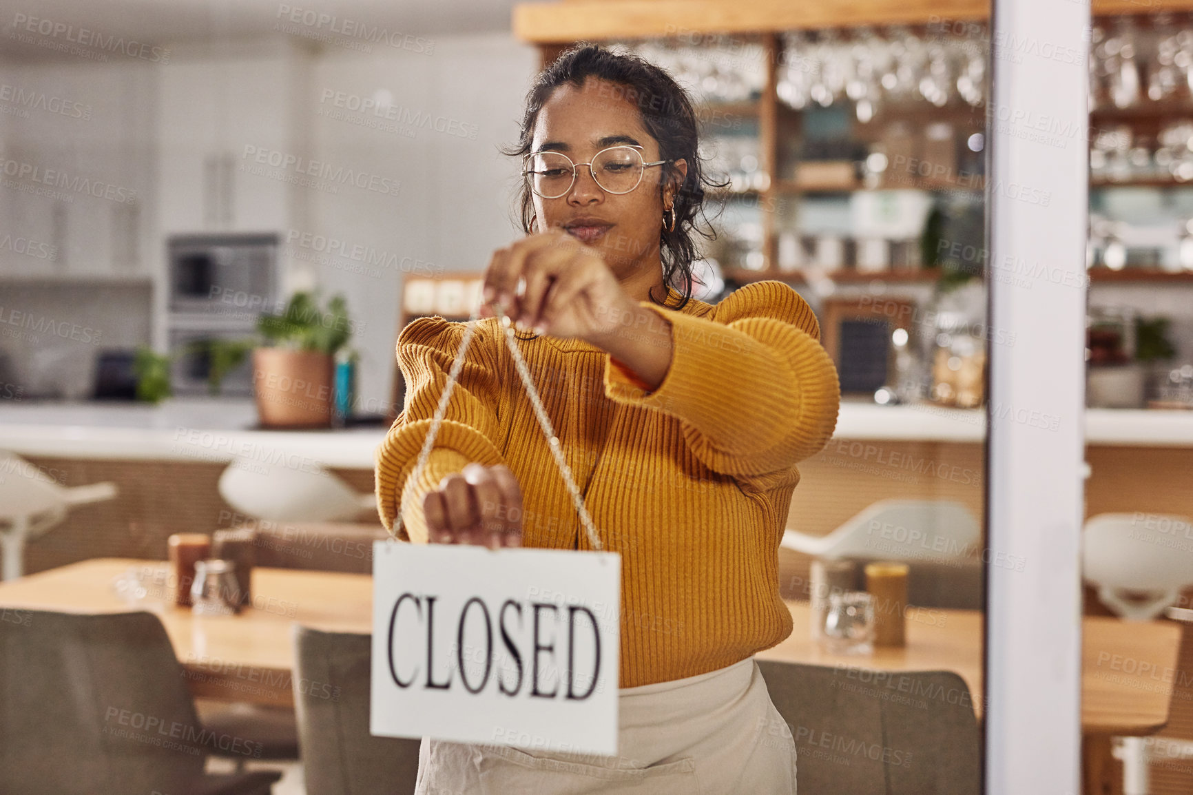 Buy stock photo Shot of a cafe owner hanging up a closed sign