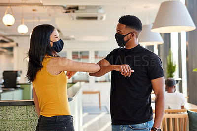 Buy stock photo Shot of a masked young businesswoman and businessman bumping elbows in a modern office