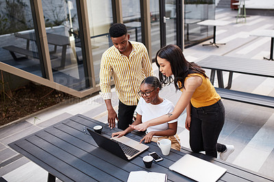 Buy stock photo Shot of a group of young businesspeople using a laptop during a meeting outside of an office