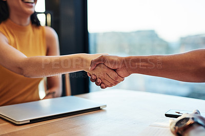 Buy stock photo Shot of a of young businesswoman and businessman shaking hands during a meeting in a modern office