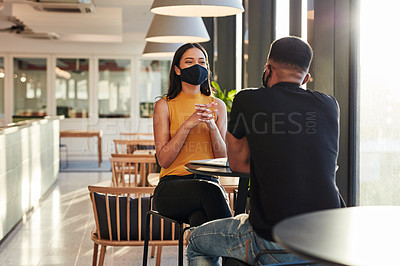 Buy stock photo Shot of a masked young businessman and businesswoman having a meeting in a modern office
