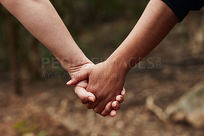 Buy stock photo Cropped shot of two women holding hands outdoors