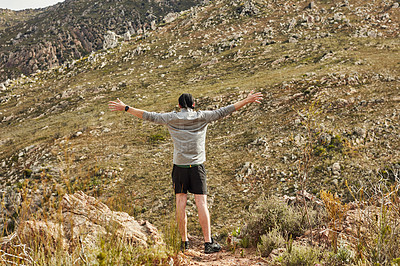 Buy stock photo Rearview shot of a young man celebrating while out hiking in nature