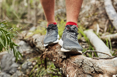 Buy stock photo Cropped shot of an unrecognisable man walking on a log along a hiking trail