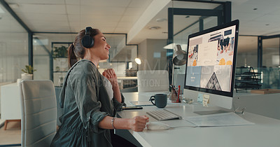 Buy stock photo Shot of a young designer wearing headphones while working on a computer in an office at night