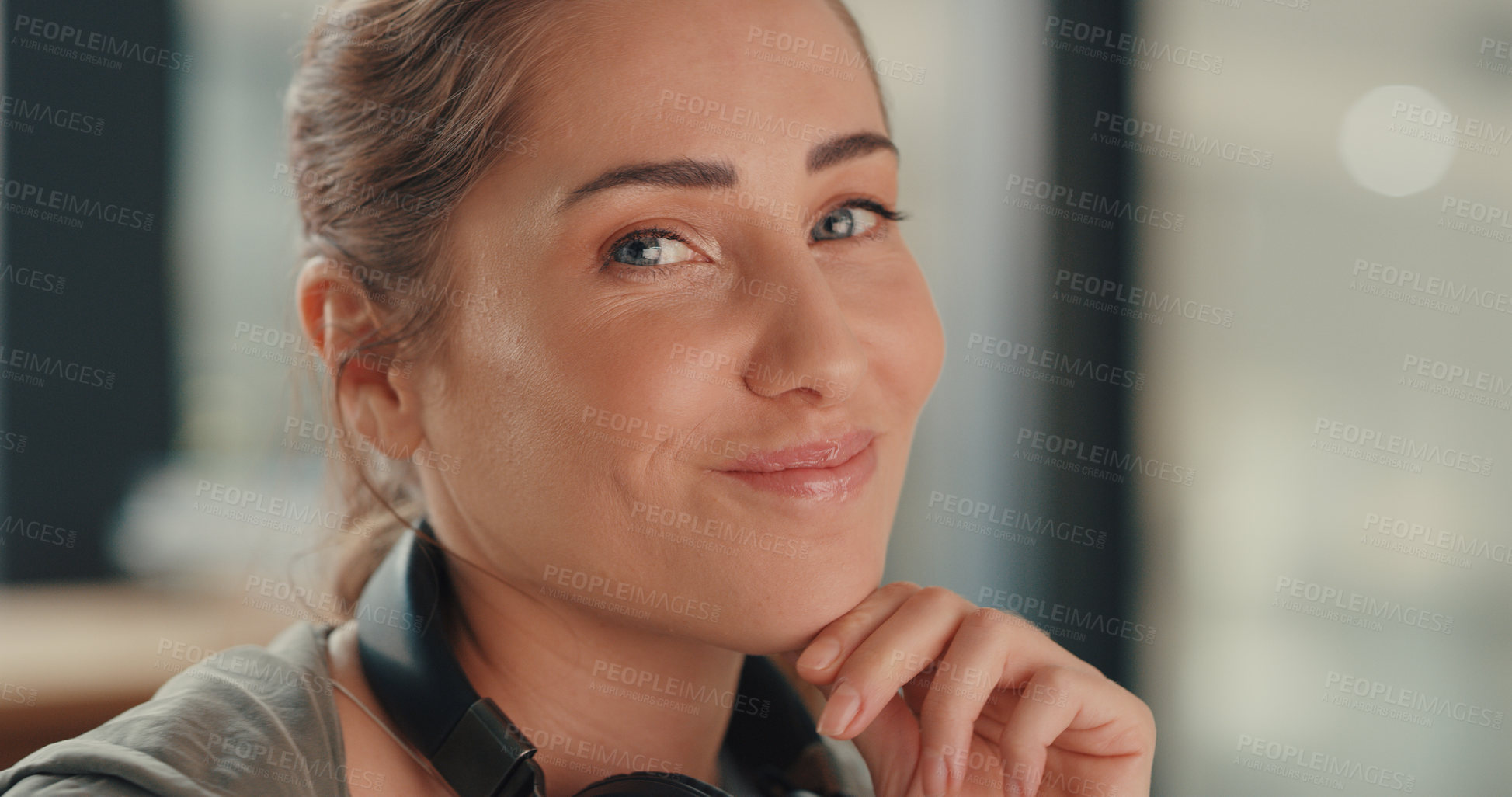 Buy stock photo Portrait of a young designer wearing headphones around her neck while working in an office