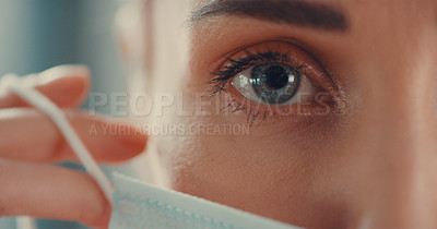 Buy stock photo Portrait of a young woman putting on a medical face mask
