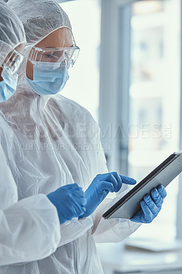 Buy stock photo Shot of two scientists using a digital tablet together in a laboratory