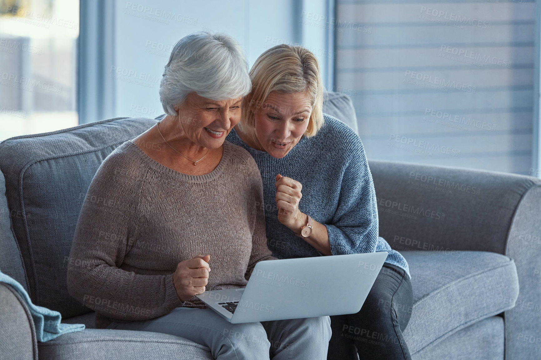 Buy stock photo Shot of a senior woman and her daughter looking surprised while using a laptop on the sofa at home