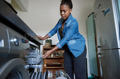 Buy stock photo Cropped shot of a young woman using her dishwasher at home