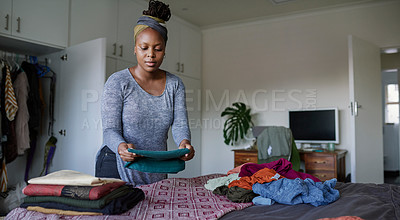Buy stock photo Cropped shot of a young woman folding her laundry at home