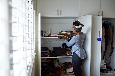 Buy stock photo Cropped shot of a young woman packing away clean laundry at home