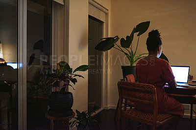 Buy stock photo Rearview shot of a young woman using a laptop at home at night