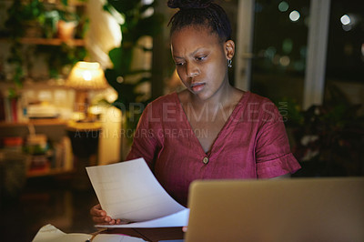 Buy stock photo Shot of a young woman going through paperwork while using a laptop at home at night