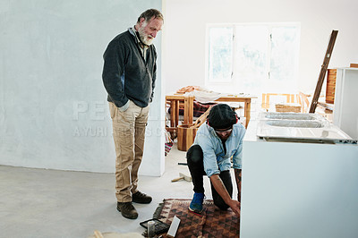 Buy stock photo Shot of a young handyman installing a kitchen sink on an elderly man's home