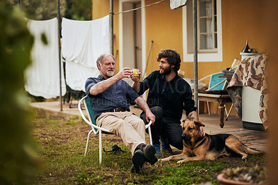 Buy stock photo Full length shot of a handsome young man and his elderly father toasting while sitting outside