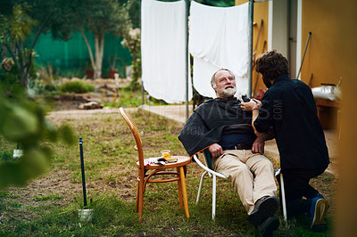 Buy stock photo Full length shot of an elderly man getting a haircut and beard trim from his son outdoors