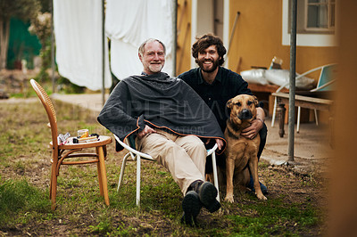 Buy stock photo Full length portrait of a handsome young man sitting outside with his elderly father and his dog