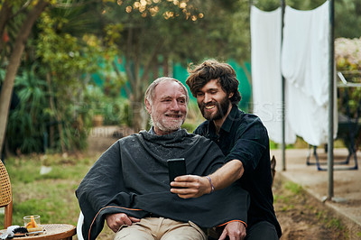 Buy stock photo Cropped shot of a handsome young man taking selfies with his elderly father while sitting outside