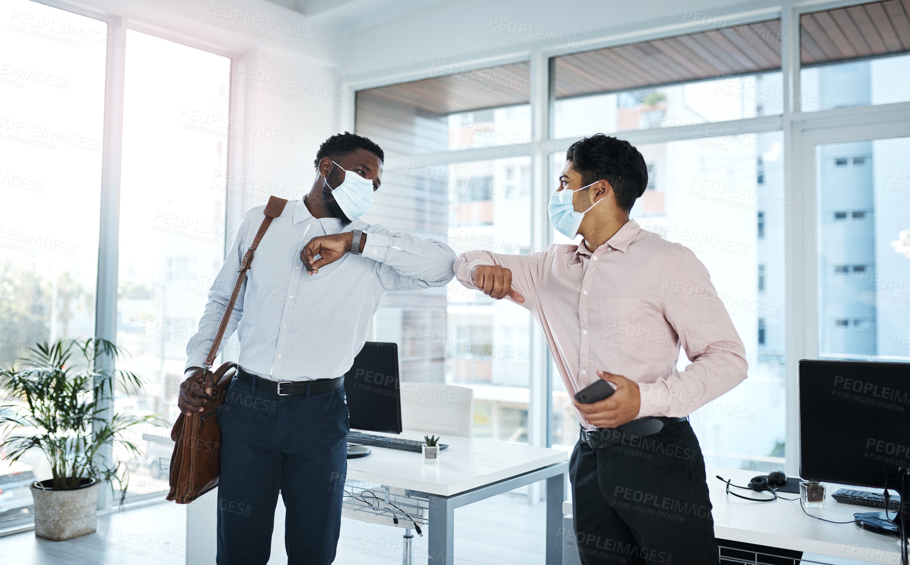Buy stock photo Shot of two businessmen bumping elbows in an office
