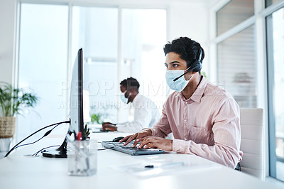 Buy stock photo Shot of a young call centre agent wearing a face mask while working on a computer in an office