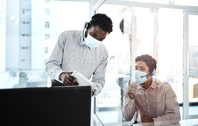 Buy stock photo Shot of two call centre agents working together in an office