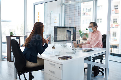 Buy stock photo Shot of two businesspeople wearing face masks while working together in an office