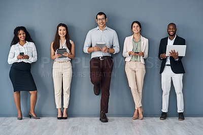 Buy stock photo Portrait of a group of businesspeople using digital devices while standing in line against a grey background