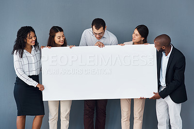 Buy stock photo Portrait of a group of businesspeople holding a black poster while standing against a grey background