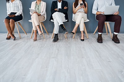 Buy stock photo Closeup shot of a group of unrecognisable businesspeople using digital devices while sitting in line against a grey background
