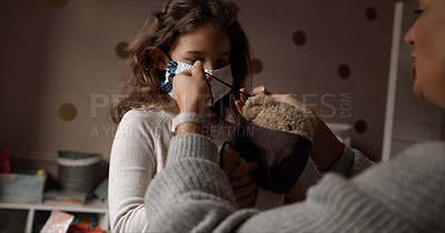 Buy stock photo Cropped shot of a woman and her young daughter putting a mask on a teddy bear in the bedroom at home