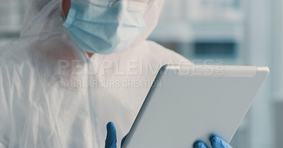 Buy stock photo Shot of a doctor wearing a hazmat suit and using a digital tablet