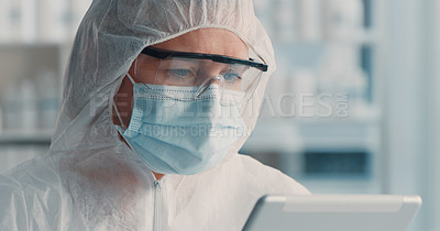 Buy stock photo Shot of a mature doctor wearing a hazmat suit and using a digital tablet