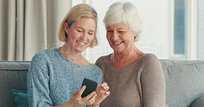Buy stock photo Shot of a senior woman and her daughter using a smartphone on the sofa at home
