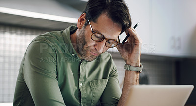 Buy stock photo Cropped shot of a man using his laptop while sitting at home