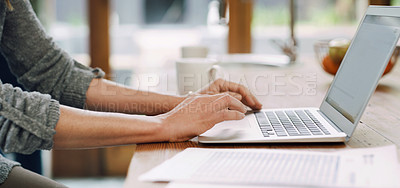 Buy stock photo Cropped shot of an unrecognizable woman using her laptop while sitting at home