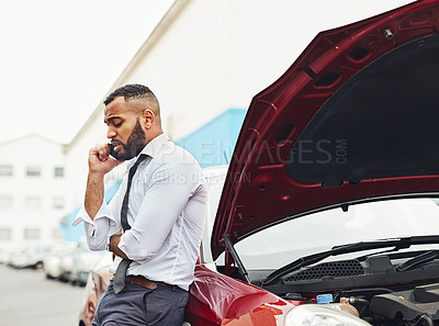Buy stock photo Shot of a man calling roadside assistance after breaking down
