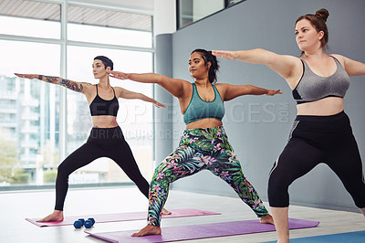Buy stock photo Shot of a group of young women practicing yoga in a fitness class